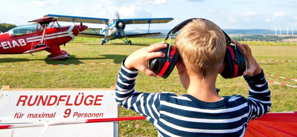 Bild: Kind mit Gehörschutz vor Flugzeug