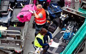 Bild: Flughafenmitarbeiter sortieren Koffer auf dem Vorfeld